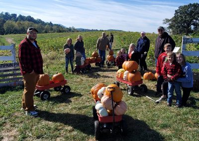 A family gathering their pumpkins